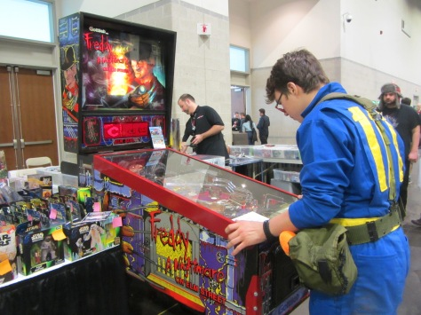 "A Terror Con attendee playing a vintage ""A Nightmare on Elm Street"" pinball game."